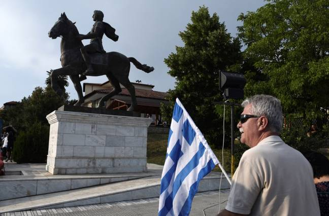 A man holds a Greek flag next to a statue of Alexander the Great. Credit: PA