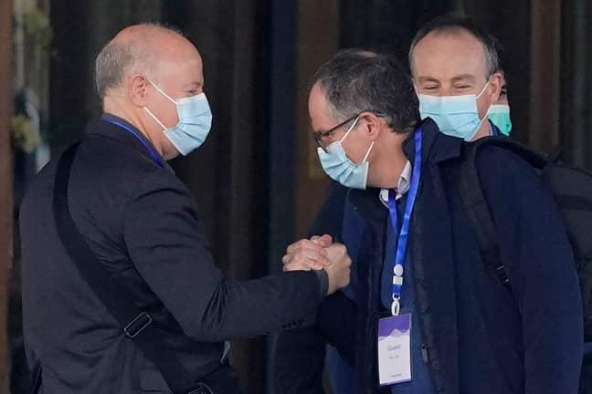 Peter Daszak, left, clasps hands with Peter Ben Embarek. Credit: PA