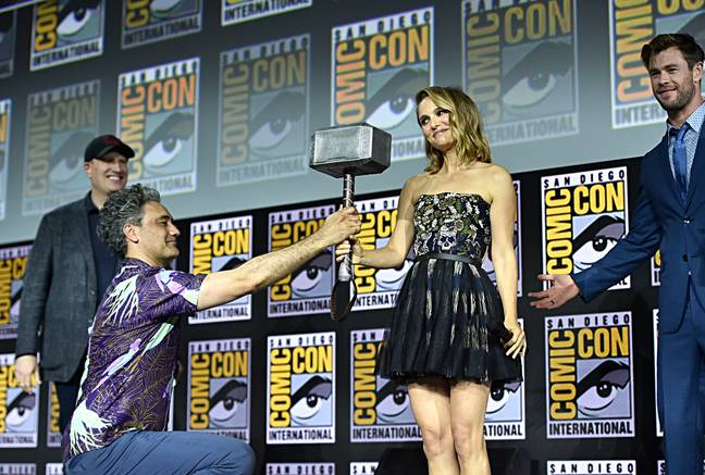 Natalie Portman being handed Thor's hammer at an event for Thor: Love and Thunder (Credit: IMDb)