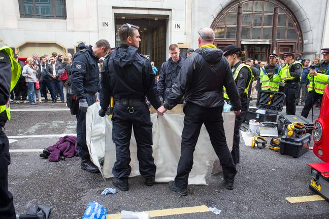 Police can be seen using screens to cover the woman. Credit: Jamie Lorriman