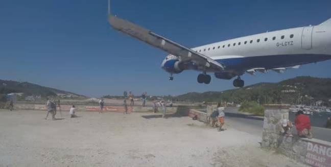 The short runway means planes fly right over tourists' heads. Credit: YouTube/Cargospotter