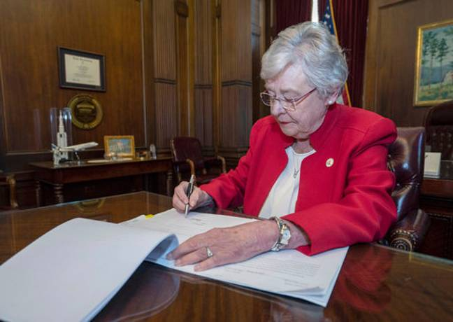 Alabama Gov. Kay Ivey signing a bill that virtually outlaws abortion in the state. Credit: PA