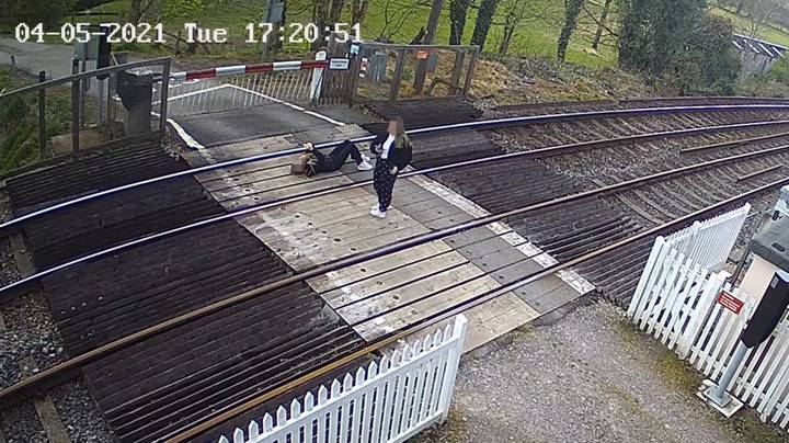 Shocking Moment Girl Lies On Train Tracks While Using Phone