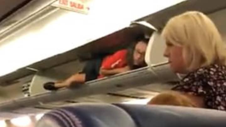 Passengers Left Baffled After Flight Attendant Climbs Into Overhead Lockers