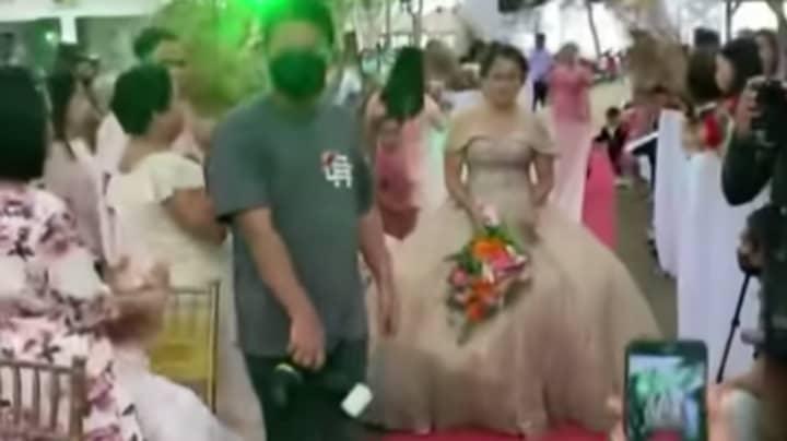 Man Hides Under Bride's Wedding Dress to Help Her Walk Amid Strong Winds